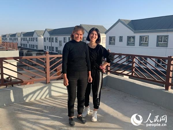 Kuwahan Mettursun and her daughter pose for photos in front of their new home. (Photo by Yang Rui/People's Daily Online)