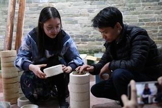 Tu Jinge (left) talks with a craftsman about technological process of making porcelain leaf cups. (Photo/Courtesy of Tu Jinge)