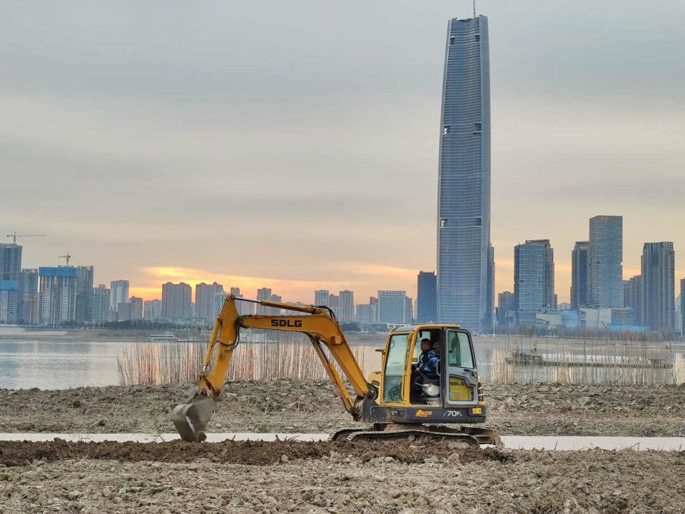 Photo taken on Jan. 9, 2021 shows an excavator removing sand and digging a ditch beside the Yangtze River in the Hankou waterfront in Wuhan, central China's Hubei province. (Photo by Li Changlin/People's Daily Online)