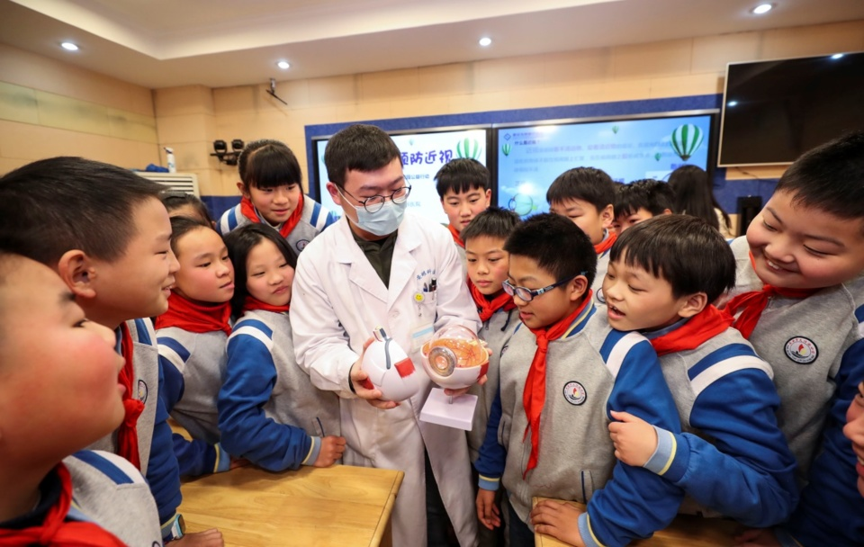 An ophthalmologist introduces the structure of eyes to students of a primary school in Huai'an, east China's Jiangsu Province, Dec. 16, 2020. (Photo by Zhao Qirui/People's Daily Online)