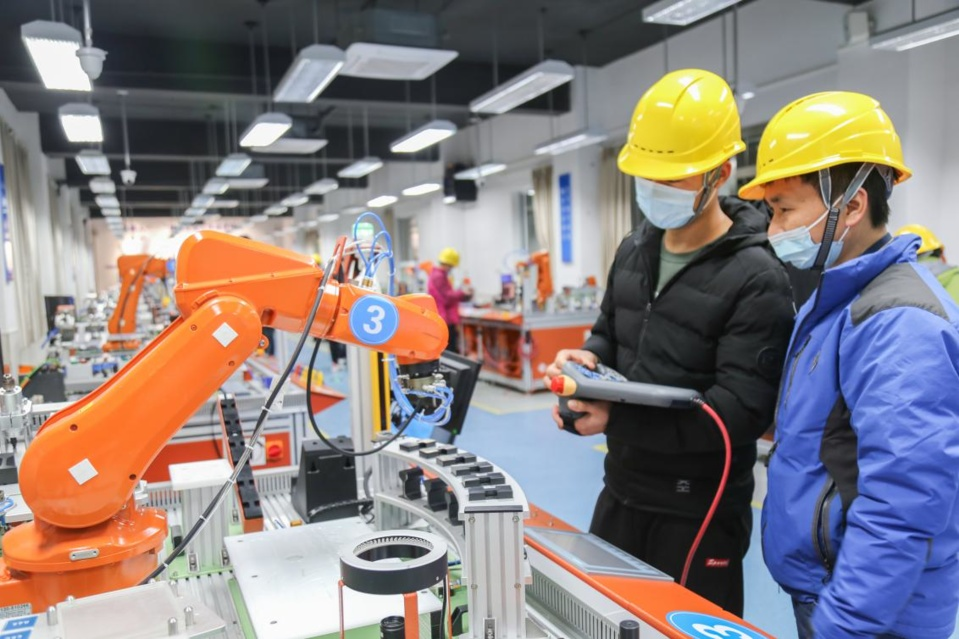 Students control a robot at the industrial robot practical training center of a vocational school in Xinqiao township, Songjiang district, east China's Shanghai, March 7, 2021. (Photo by Jiang Huihui/People's Daily Online)