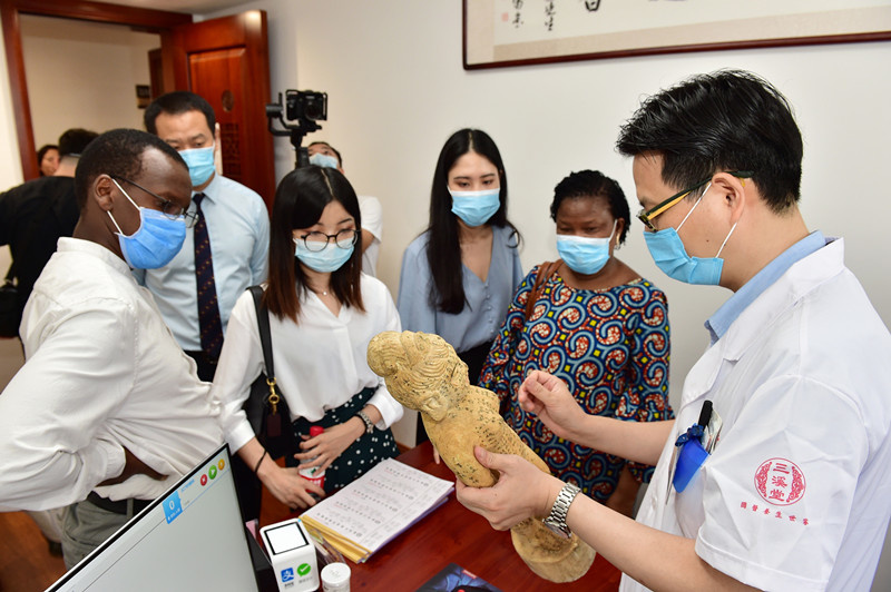 Photo taken on June 13, 2020, shows a traditional Chinese medicine (TCM) doctor explaining TCM acupuncture and moxibustion to a group of visitors led by Edwin Limo, counselor of the Embassy of Kenya in China at Sanxitang Pharmacy, a time-honored TCM pharmacy in east China's Zhejiang province. Acupuncture and moxibustion of TCM was listed as UNESCO Intangible Cultural Heritage on Nov. 16, 2010. (Photo by Lyu Bin/People's Daily Online)
