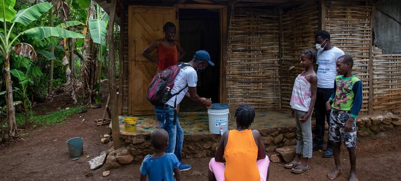 En Haïti, une équipe de l'UNICEF rend visite à une famille dans la petite ville de Dame-Marie, dans le département de Grand'Anse, pour sensibiliser à la Covid-19. © UNICEF/Haiti