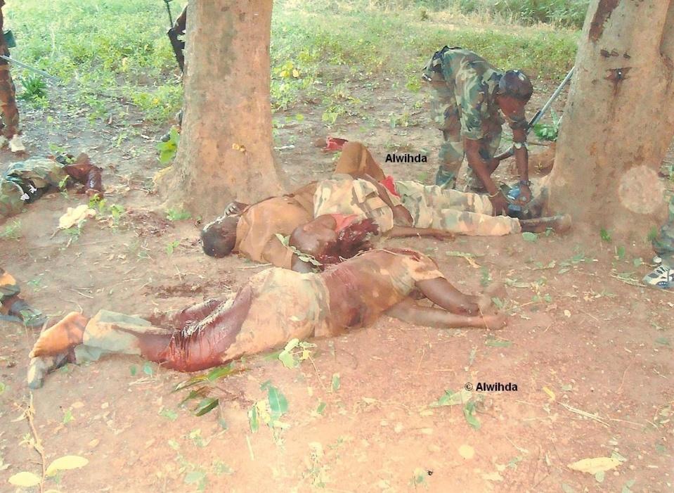 Un combattant enlève la chaussure d'un soldat des FACA tué au combat. © Alwihda Info