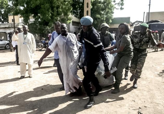 AFP/AFP - Des forces de sécurité évacuent un corps après un attentat-suicide à Maroua, la capitale de l'Extrême-nord du Cameroun, le 22 juillet 2015