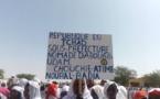 Une femme brandit une pancarte lors de la journée internationale de la femme rurale à Abougoudam. Alwihda Info/D.H.