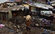 Un habitant d'un bidonville de Freetown transporte des objets récupérés dans une décharge, le 28 mars 2018 / © AFP/Archives / ISSOUF SANOGO