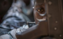 Un enfant-soldat regarde à travers la crosse d'un fusil au cours d'une cérémonie de libération à Yambio, au Soudan du Sud, le 7 février 2018 / © AFP/Archives / Stefanie Glinski